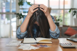 stressed woman accounting home expenses and calculate credit card monthly debt to bills payment.