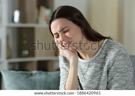 Stressed woman complaining suffering toothache sitting on a couch at home Сток-фото ©