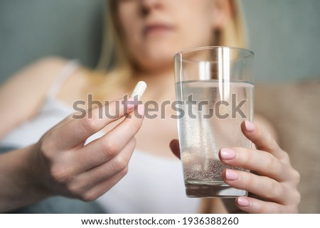 Stressed woman drinking white round pill while sitting in bed with glass of water in hand. Tired young lady takes medicines after wake up in the morning, tries to overcome insomnia with sleeping pill Foto stock ©