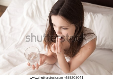 Stressed woman drinking white round pill while sitting in bed with glass of water in hand. Tired young lady takes medicines after wake up in the morning, tries to overcome insomnia with sleeping pill