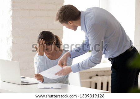 Stressed woman gets scolding from boss. People at work. Conflict between employer, employee. Angry boss criticizes report of colleague. Manager gives dismissal notice to worker. Upset woman gets fired