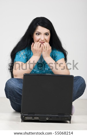 Stressed woman  looking scared and biting her nails in front of laptop