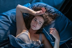 Stressed woman on bed late at night suffering from insomnia, sleep apnea or stress. Top view of depressed girl lying in bed late at night. High angle view of awake girl in the middle of the night.