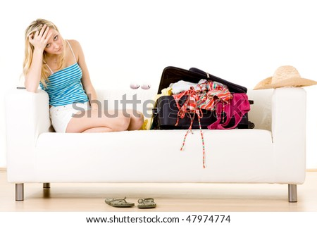 Stressed woman on couch packing for holiday.