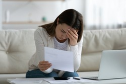 Stressed woman sit on sofa read bad news notification paper letter from bank about debt or eviction, calculate domestic bills has financial problems feels worried, lack of finances, bankruptcy concept