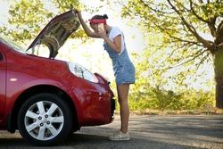 Stressed woman talking on phone near broken car outdoors