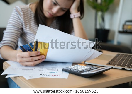 stressed woman trying money to pay credit card debt and many expenses bills such as electricity bill,water bill,internet bill,phone bill during covid-19 or coronavirus outbreak at home