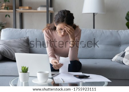 Stressed woman wearing glasses checking bills, feeling anxiety about debt or bankruptcy, lack of money, unhappy female sitting on couch at table with laptop, holding receipt, planning budget Stock photo ©