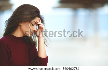 Shutterstock Stressed Woman with Headache on the Beach. Outdoor Sad Woman