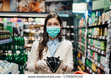 Stressed woman with mask shopping in grocery store with an empty wallet.Bankruptcy/recession.Covid-19 quarantine lockdown impact.Unemployed person in money crisis.Financial hardship.No income anxiety