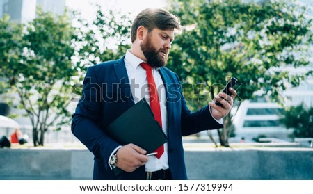 Stressed worrying bearded businessman wearing suit looking at mobile phone reading message and texting standing on street near business center with folder in hand