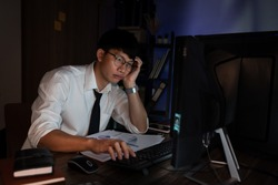 Stressed Young asian business man working late night alone in office late his eyes are gonna closing at table and looking headache sleepy, overtime overload working concept.