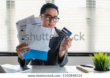 Stressed young asian businessman holding so many expenses bills electricity bill,water bill,internet bill,cell phone bill and credit card bill in his hand no money to pay debt