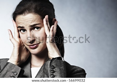 Stressed young business woman having headache.
