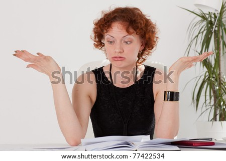 Stressed young businesswoman sits at a table  in the office.