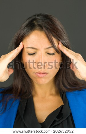 Stressed young businesswoman suffering from headache