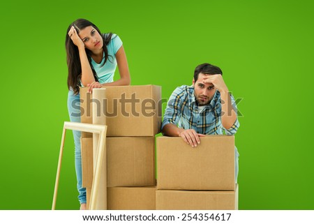Stressed young couple with moving boxes against green vignette