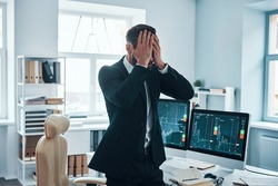 Stressed young man in formalwear covering face with hands while working in the office
