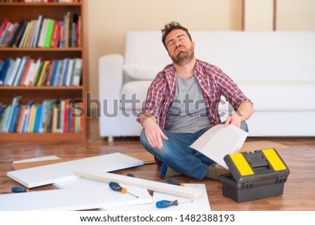 Stressed young man reading the instructions to assemble furniture
