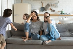 Stressed young parents sitting on couch, tired of crazy loud hyperactive little children siblings at home. Unhappy married couple irritated by naughty small kid son daughter, suffering from headache.