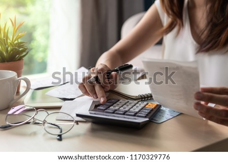 Stressed young woman calculating monthly home expenses, tax, bank account balance and credit card bills payment, Income is not enough for expenses. Photo stock ©