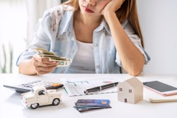 Stressed young woman calculating monthly home expenses, taxes, bank account balance and credit card bills payment, Income is not enough for expenses