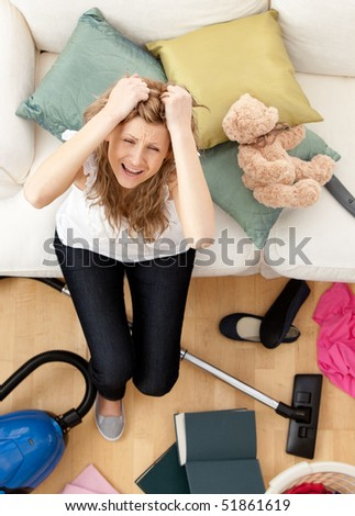Stressed young woman doing housework in the living-room