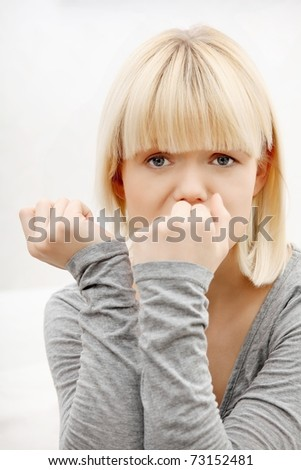 Stressed young woman eating her nails at home