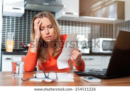 stressed young woman is doing banking and administrative work holding bills at home
