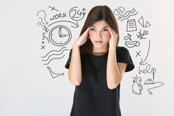Stressed young woman on light background