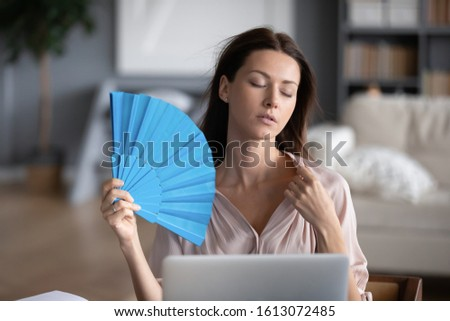 Stressed young woman sit at desk in living room feel warm use hand waver, unwell sick millennial girl wave fresh air at home suffer from hot weather, lack of air condition, heatstroke concept
