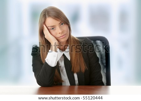 Stressed young woman sitting behind a desk
