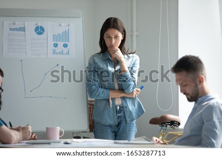 Stressed young woman standing near flipchart, feeling nervous before presentation. Thoughtful female brunette speaker touching chin, remembering or repeating mentally speech before performance.