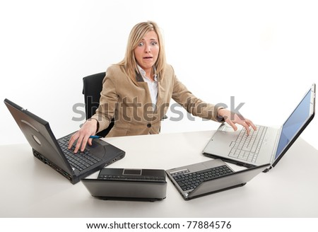Stressed young woman using four laptops