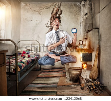 Stressful Businessman levitating in yoga lotus pose with alarm clock in his hand in old Russian house with traditional stove