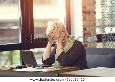Stressful day. Feeling tired and stressed. Frustrated adult woman keeping eyes closed from fatigue while sitting in office at her working place. Woman thinking about to complete work task.