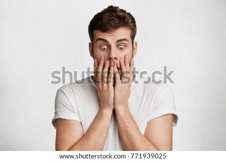 Stock Photo Stressful terrified young attractive male with beard, covers mouth and looks with eyes popped out down, being shocked noticing huge spider on floor, expresses negative emotions and frightening