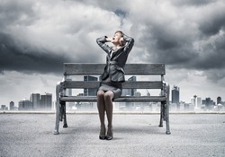 Stressful woman sitting on wooden bench. Emotional screaming girl keeps hands on head. Businesswoman in despair on background modern cityline panorama with cloudy storm sky. Woman call for help.