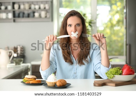 Stressful woman with taped mouth and different products in kitchen. Choice between healthy and unhealthy food #1181403529