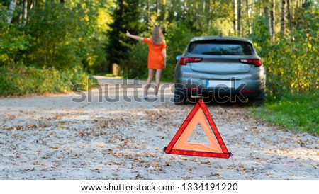 Stressful young woman driver hitchhikes and stops cars, asks for help as have problem with brocken car, uses red triangle sign to warn drivers about stop.  (selective focus)