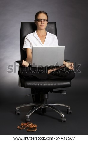 Stressless at work: Attractive office woman sitting in office chair in yoga lotus posture with laptop on her lap. - stock photo
