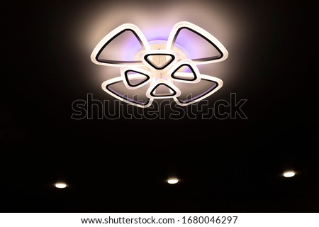 stretch ceiling in white. A decorative chandelier hangs in the center. Zdjęcia stock ©