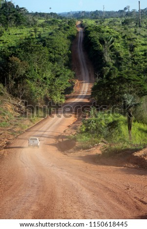 stretch of the unpaved transamazonic highway (BR-230) surrounded by dense Amazon forest #1150618445