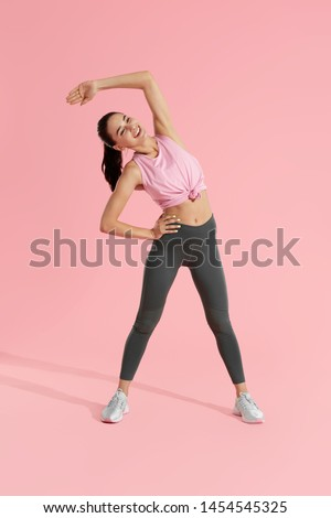 Stretch. Sport woman stretching body, warming up on pink background. Full length portrait of sporty girl, fitness model in sportswear doing warm up workout at studio