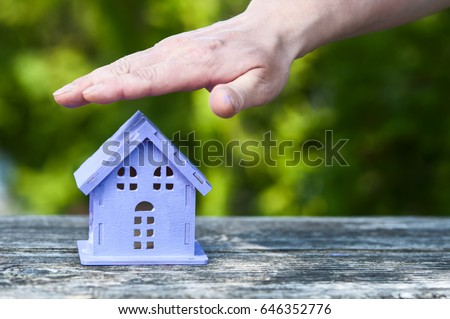 stretched hand over a toy house of lavender color, as a symbol of safety #646352776