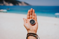 Stretched hand palm with black metal compass against summer beach and blue sea. Follow your way, goal, wish concept. Point of view pov