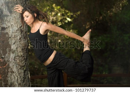 Stretching in the woods / Attractive young woman leaning on a tree stretching in the woods.