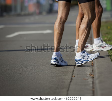 Stretching muscles of leg just before starting the long distance running race marathon