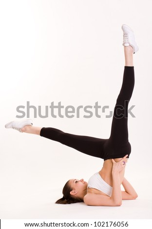 Stretching out, portrait of flexible young brunette fitness woman posing.