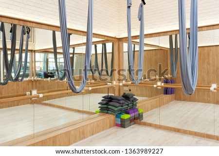 Stretching studio interior with aerial yoga silk hammocks and mirrors